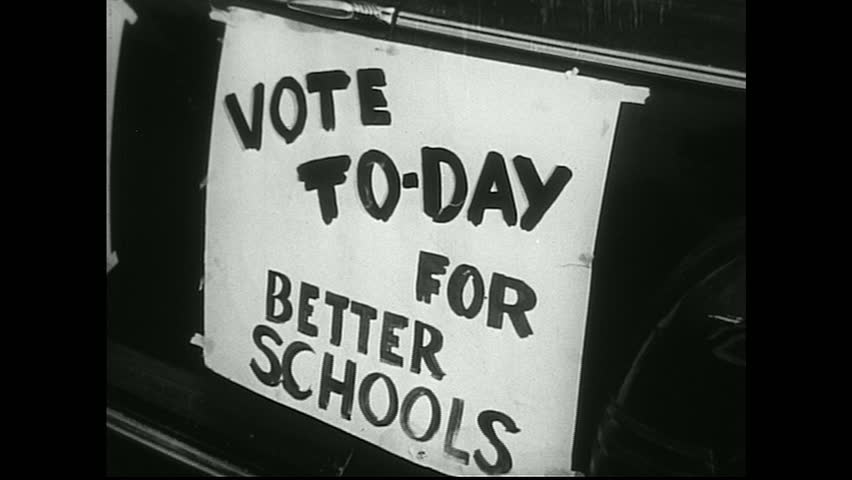 """United States 1950s. Sign on car reads """"Vote Today For Better Schools."""" People in line. Newspaper headline about school board."""