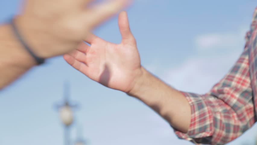 Shaking hands between friends. Friendship handshake outdoor. Two good guys are shaking hands and fists when meeting.