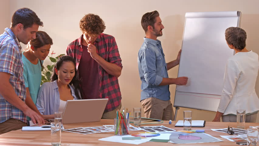 Creative business team working on laptop while their colleagues looking at white board in office   Shutterstock HD Video #11456456