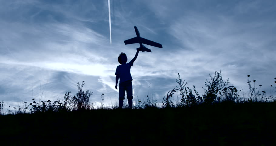 Boy playing outside with toy airplane silhouetted slow motion