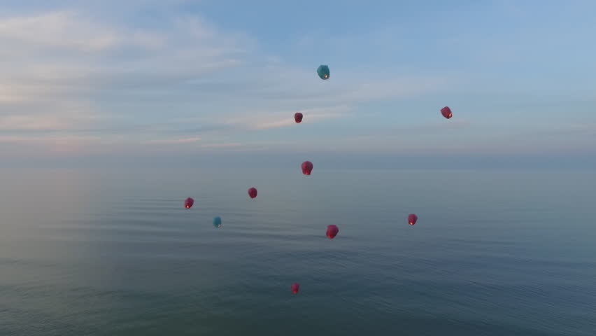Chinese lanterns flying in the air over the ocean and mountains. On the Sunset . | Shutterstock HD Video #11475194