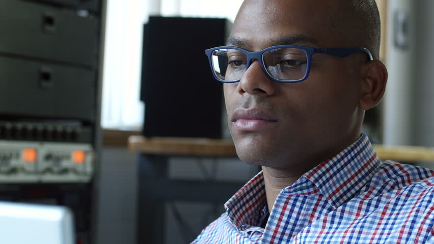 Young black male office worker at the computer in an office