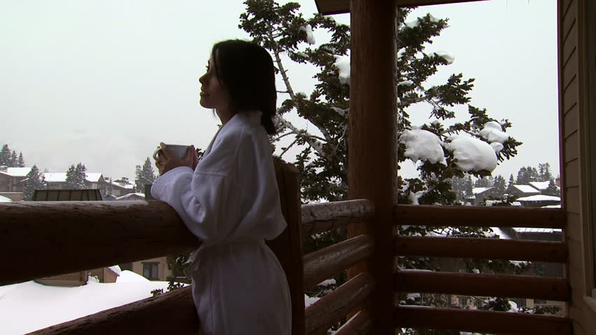 A woman on a snowy balcony drinking coffee | Shutterstock HD Video #11481605
