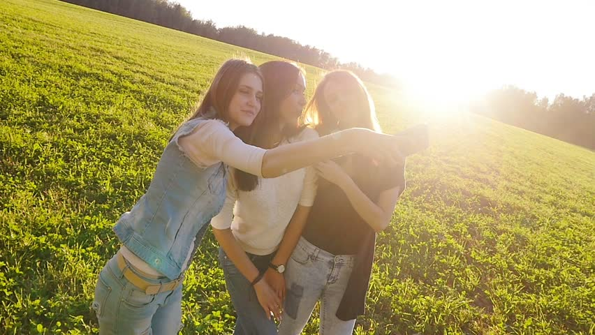 Three friends, young pretty girls, caucasians, having fun outdoors in fields on sunset, making selfie, slow motion. #11489759