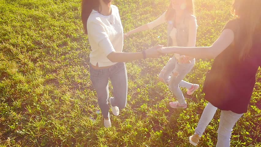 Three friends, young pretty girls, caucasians, having fun outdoors in nature, spinning around in roundelay, slow motion. #11519204
