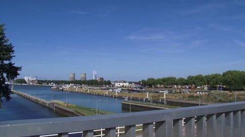 LOCK COMPLEX MAASBRACHT, THE NETHERLANDS - AUGUST 2015: Skyline city of Maasbracht + inland port + pan higher situated Lock complex with video surveillance.