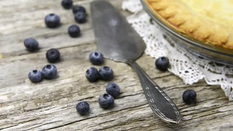Tracking dolly shot right of freshly baked blue berry pie with lace doily and silver pie lifter