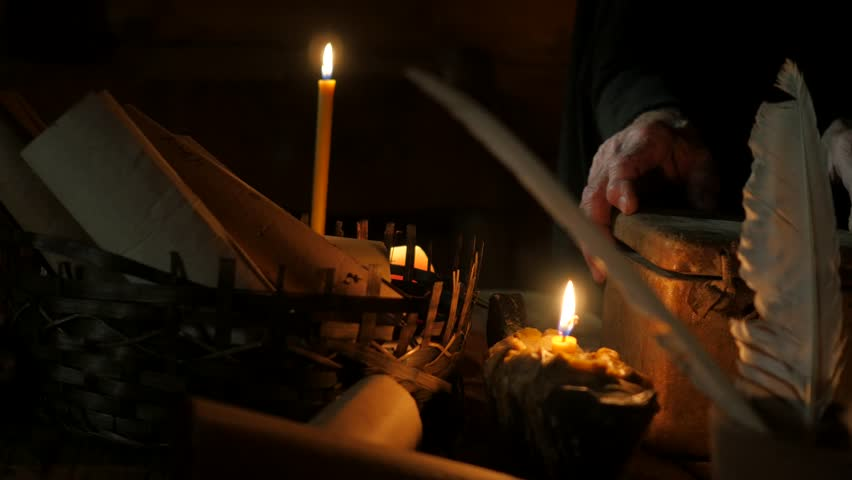 Dark Room in an old log hut of the 11th century. Candlelight. Writing Tools on Table, Old man, monk, chronicler, dressed in black robe, in the hood. Nestor the Chronicler. Man writes with a quill pen