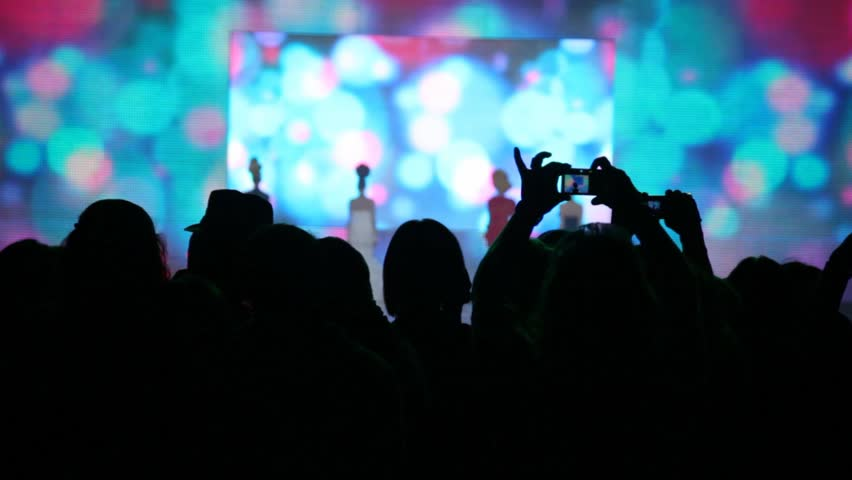 Silhouette of people who look a concert of popular music and records it on camera #1156828