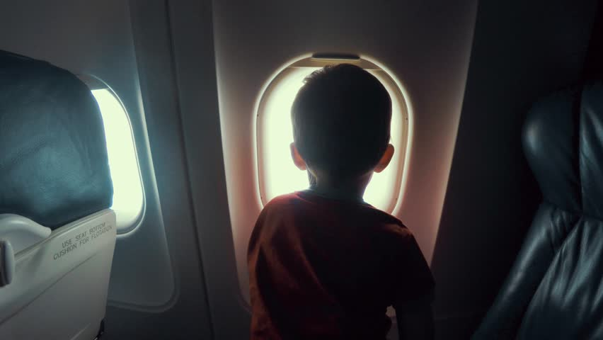 A young boy sitting on the seat looking out an airplane window while flying | Shutterstock HD Video #11576981