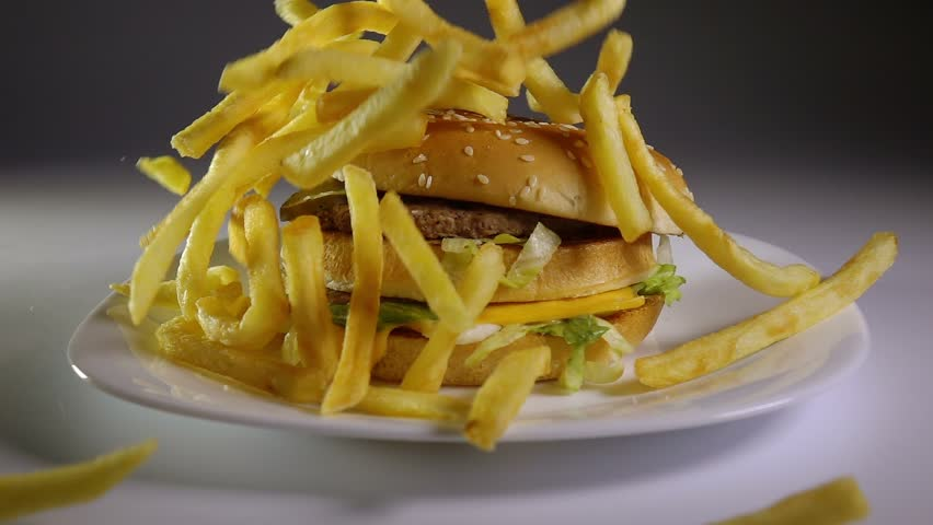 Fried potato chips falling down on hamburger, slow motion, fast food, junk food concept. #11605778