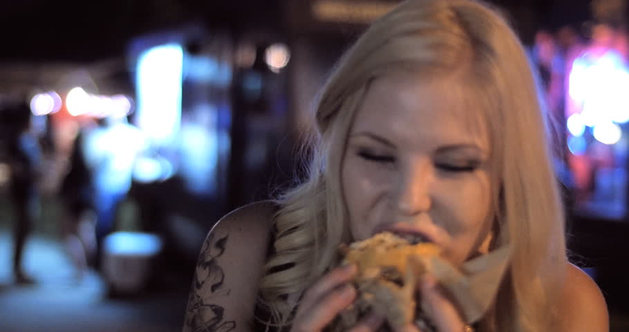 4K - A Close up shot of pretty hipster hip cool fun girl eating late night burger from a popular trendy food truck in a urban street festival setting at night.  Version 1 - shorter
