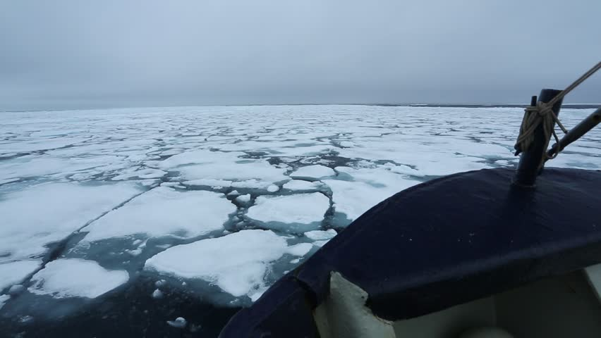 Winter coastal landscape with floating ice fragments on still dark blue sea water from the boat, Arctic, Svalbard