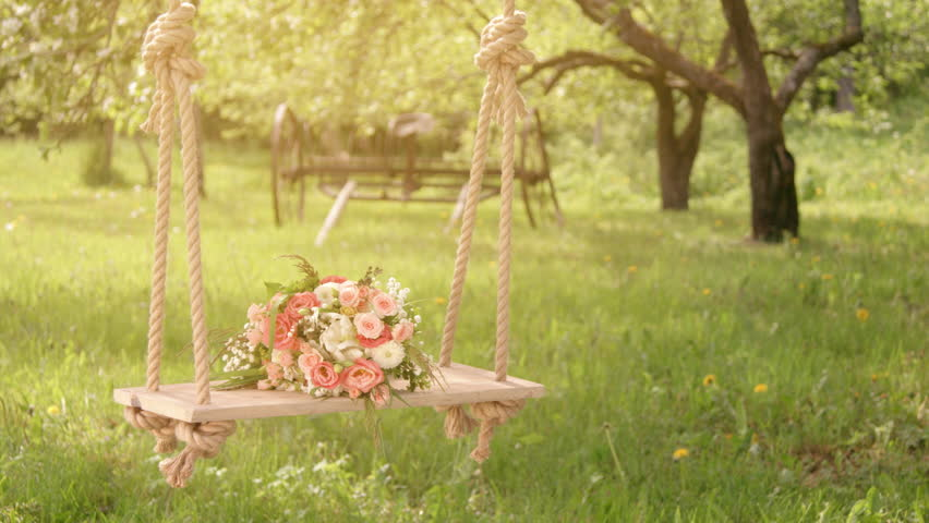 Flowers on rope swing under blossoming apple trees, sun flare