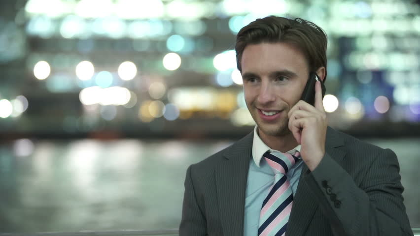 Portrait of attractive young professional man talking on mobile phone in the city at night. Shot on RED Epic | Shutterstock HD Video #11635448