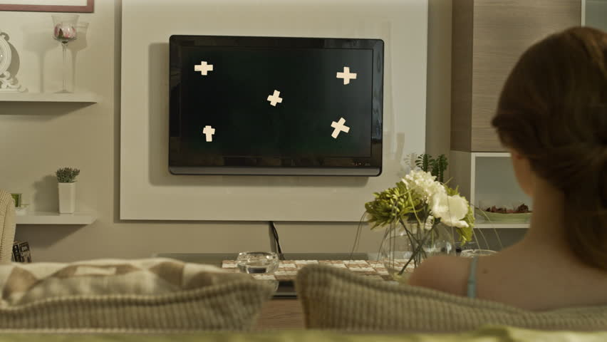 4k Rear view of young woman watches TV in the room. With tracking marks . Shot on RED EPIC Cinema Camera.