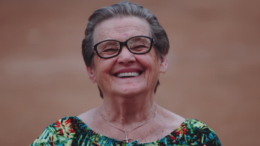 Smiling elderly woman looking at camera. Cinematic footage.