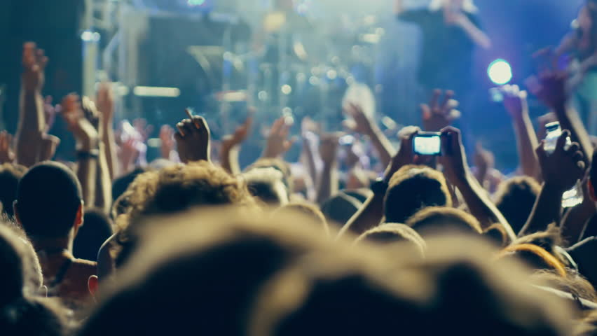 4K big crowd at concert cheering clapping hands.4k real time clip at a night rock concert showing people having fun lifting hands up in the air and applauding the musicians.