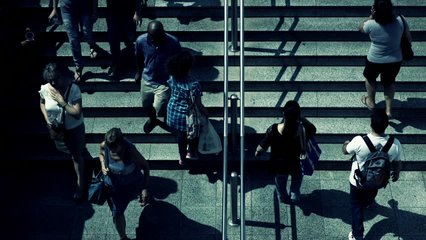 Birds eye view slow motion people walking steps to underground entrance.100-25p conformed super slow motion hd clip of an overhead view of people walking towards and away from the  train station.