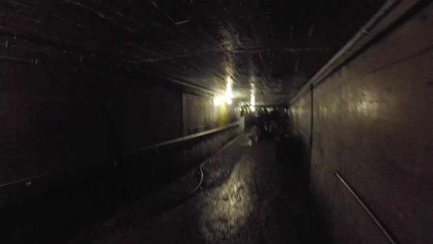 Tourists walking through a dark underground coal mine   Shutterstock HD Video #11682860