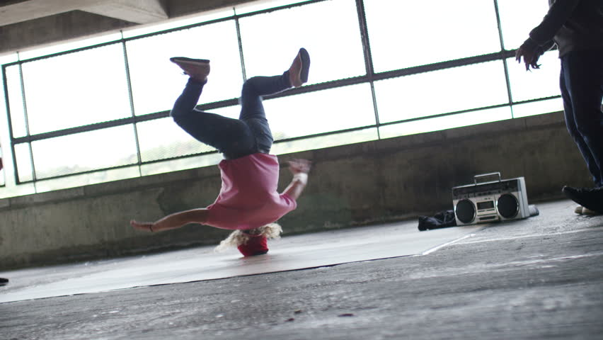 4K Female breakdancer finishes her dance moves in urban surroundings as friends cheer her on, in slow motion, shot on RED EPIC DRAGON