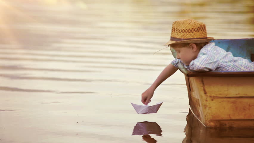 Little boy sitting in the real boat sets his paper ship off to sail | Shutterstock HD Video #11712602