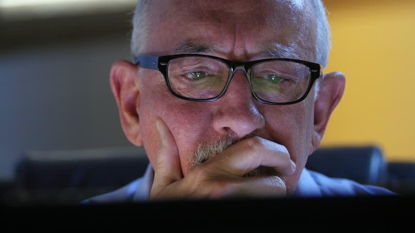 Older man talking back and upset at his computer