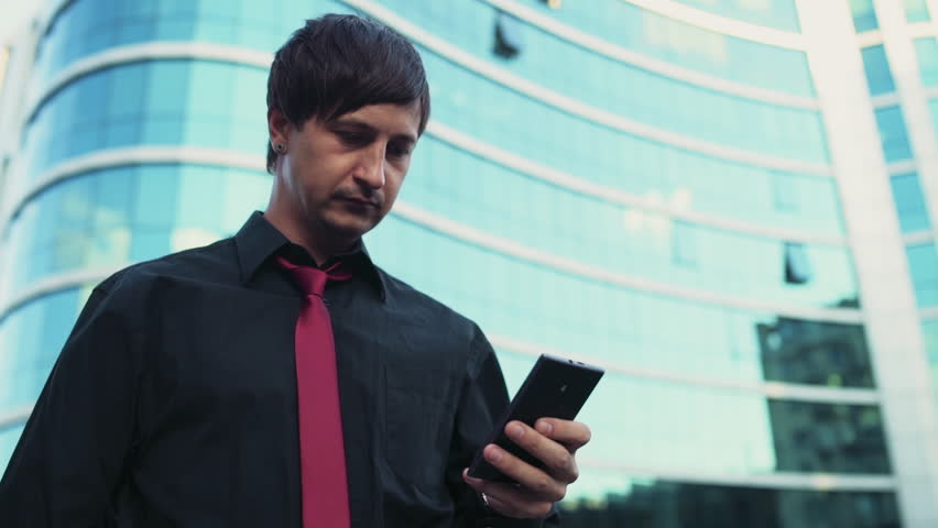 Handsome businessman using a smartphone on the street slow motion | Shutterstock HD Video #11735528