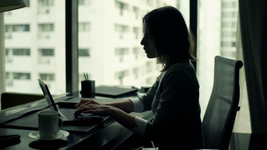 Young businesswoman using modern laptop sitting by desk office   | Shutterstock HD Video #11744390