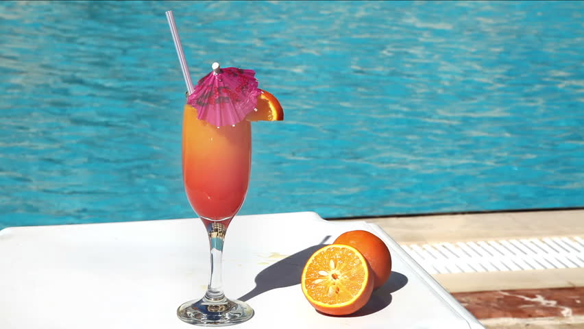 Orange Cocktail With Umbrella And Straw Near Swimming Pool Stock Footage Video 1174816