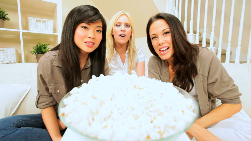Trio of girls relaxing at home with snack food enjoying a movie at home