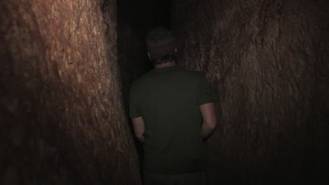 A Young Man Walks through the ancient Hezekiah's Tunnel In Jerusalem, Israel