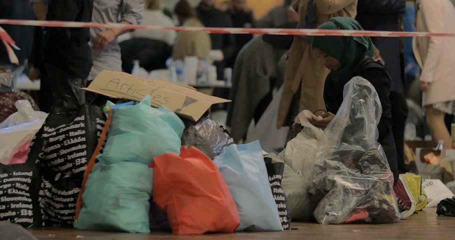 COPENHAGEN, DENMARK - SEPTEMBER 15, 2015: Young woman is choosing children's clothes from the stuff donated by locals to Syrian refugees.