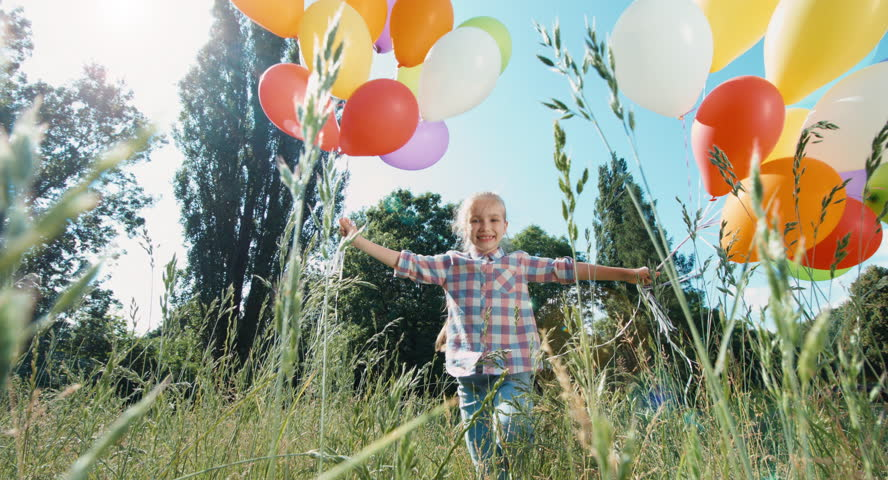 Girl child playing with balloons against the sky in the sunlight | Shutterstock HD Video #11806769