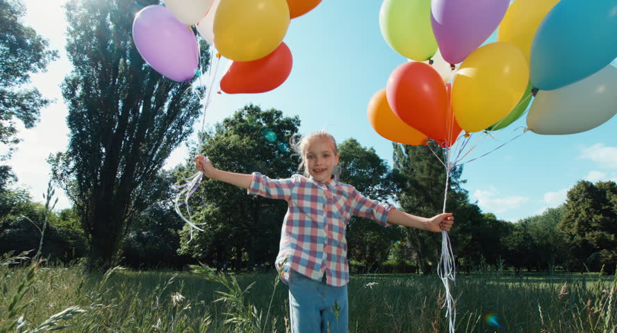 Playful portrait girl walking at camera with balloons in the park | Shutterstock HD Video #11806781