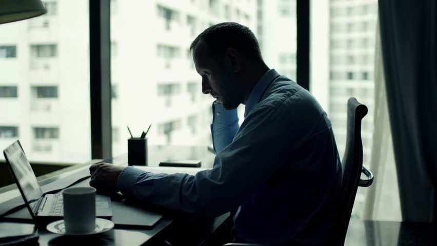 Businessman reading and analyzing documents sitting in the office