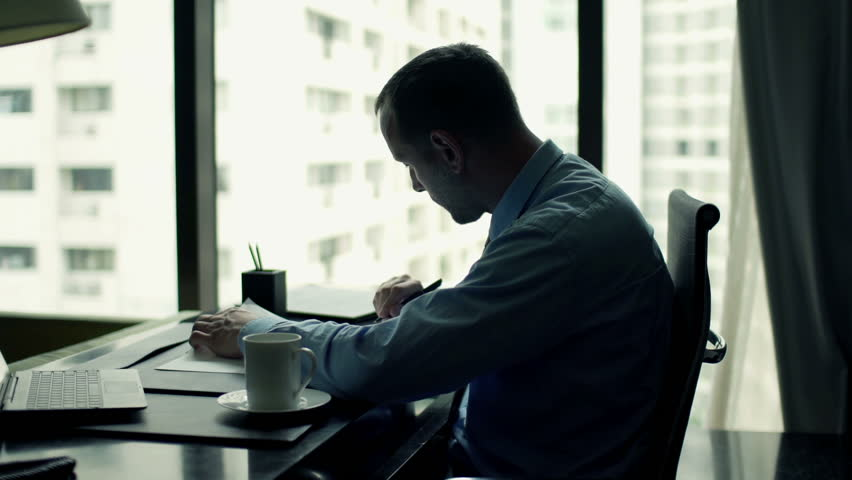 Businessman writing notes in documents sitting by table at the office