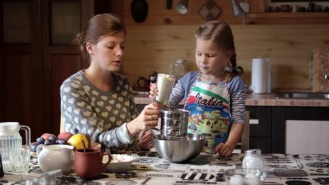 Mother and daughter cooking a pie