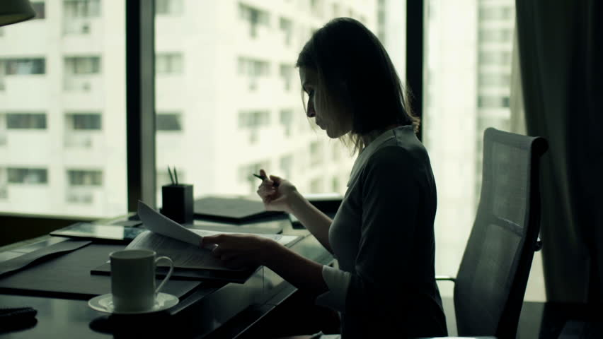 Young businesswoman writing notes in documents sitting by desk in office