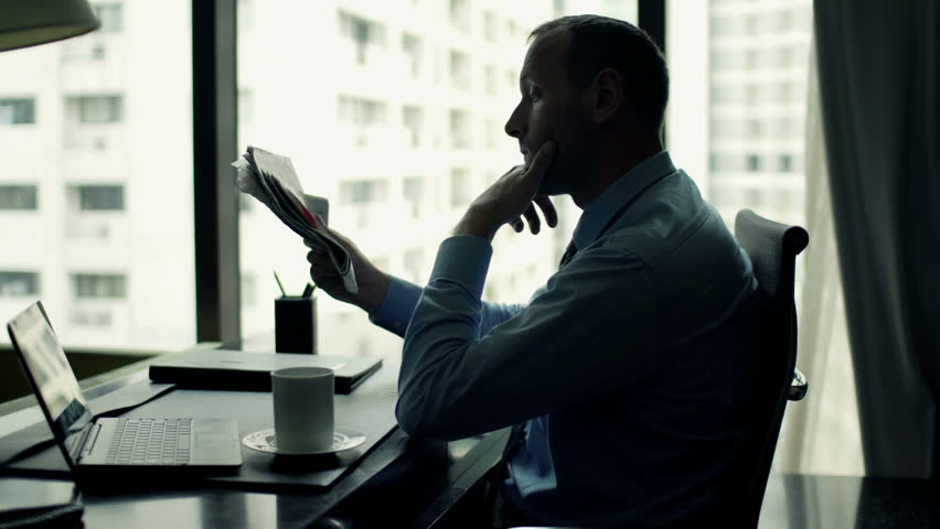 Young businessman reading newspaper and drinking coffee sitting by desk in office    Shutterstock HD Video #11827208