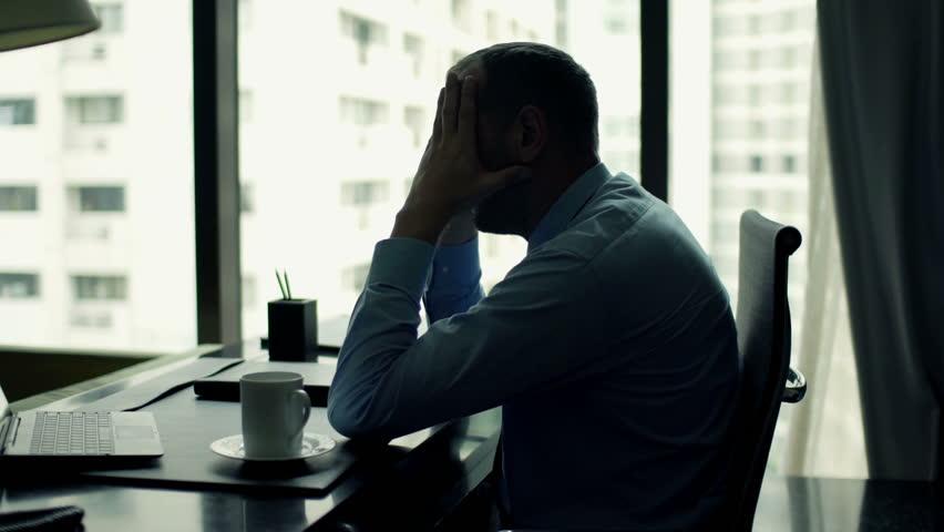 Sad, tired businessman sitting by desk in office    Shutterstock HD Video #11827325