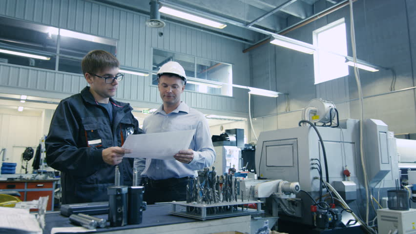 Engineer in Hard Hat and Factory Worker are Talking about Blueprint. Shot on RED Cinema Camera in 4K (UHD). | Shutterstock HD Video #11848274