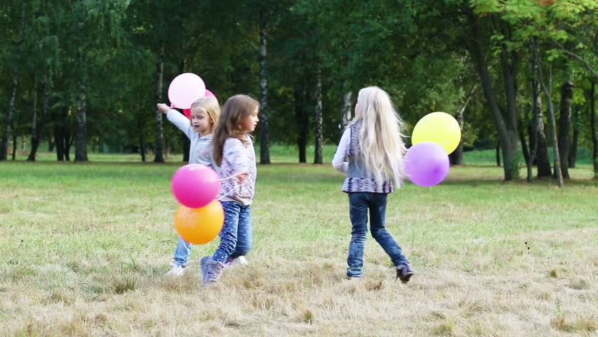 Three girls having fun running in the park with balloons | Shutterstock HD Video #11848946