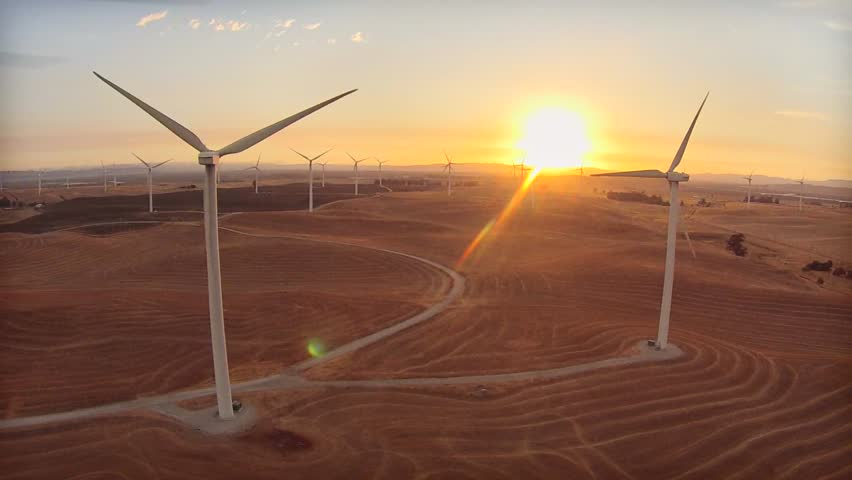 Tracking left along row of windmills looking into sunset with many windmills and mountains in the background. | Shutterstock HD Video #11855939