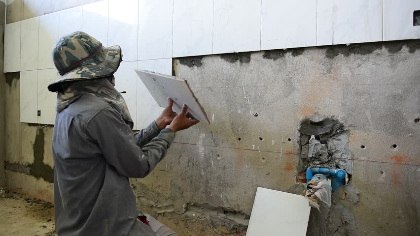 Ceramist puts tile on the wall. Professional ceramist is laying ceramic tile on the wall  #11881190