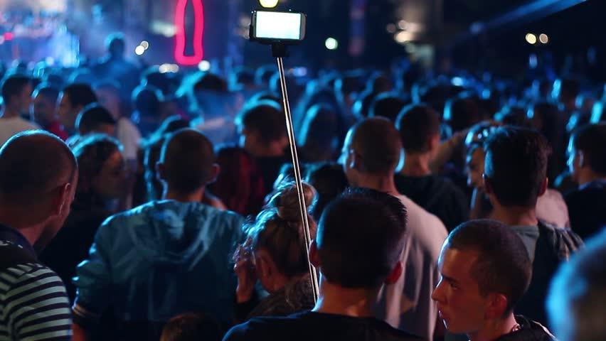 Sofia, Bulgaria - 20 September 2015: Free open air pop concert - Man using selfi pole stick shoots concert on mobile phone #11883575