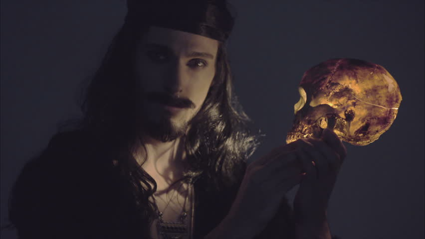 handssome magical pirate holding a death's head illuminated from inside by candle in 4K