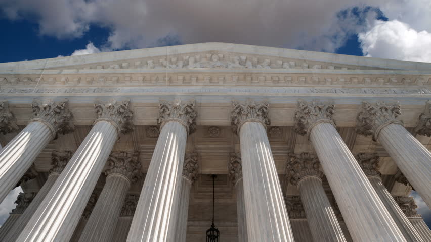 United States Supreme Court building in Washington DC with time lapse clouds.