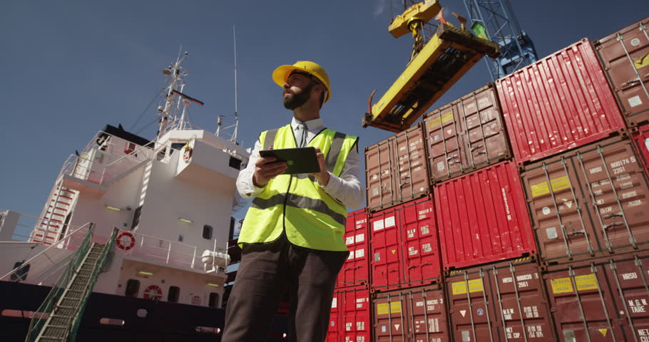 A young manager doing inspection rounds through an industrial harbor working on a digital tablet. Shot on RED Epic. Royalty-Free Stock Footage #11906468