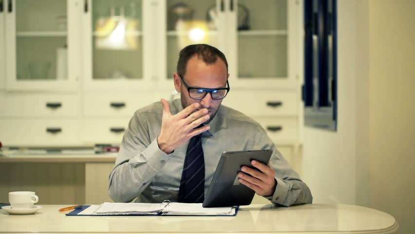 Overwhelmed businessman working with documents and tablet computer in kitchen at night  | Shutterstock HD Video #11910068